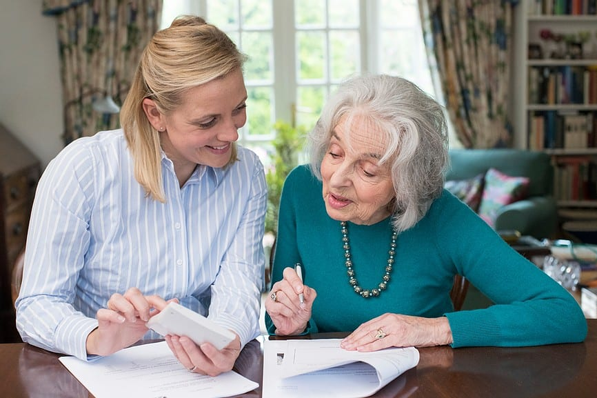Woman Helping Elderly Woman with Paperwork